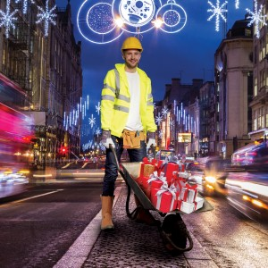 A construction worker with a wheel barrow of gifts
