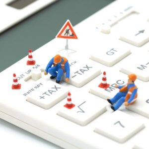 construction worker figures working on a giant calculator surrounded by cones